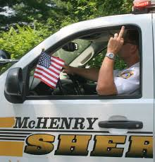 Undersheriff Andrew Zinke giving Cal Skinner the finger at the 4th of July Parade in Crystal Lake, IL.