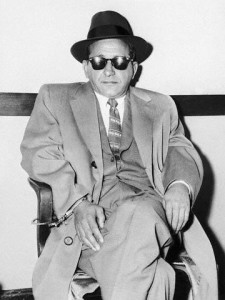 "Sam ""Mooney"" Giancana is handcuffed to a chair"